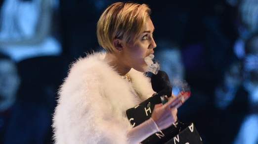 Singer Miley Cyrus smokes on stage after receiving the Best Video award during the 2013 MTV Europe Music Awards at the Ziggo Dome in Amsterdam
